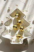 Chocolate balls wrapped in gold foil, strings of pearls