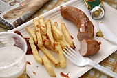 Sausage and chips on paper plate