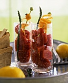 Tomato ice with tomatoes on cocktail sticks in glasses