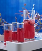 Raspberry drink in glass jug and in glasses