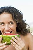 Frau isst ein Stück Wassermelone