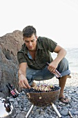 Young man turning shashlik on barbecue on beach