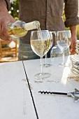 Mann schenkt Weisswein ein