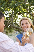 Man and woman raising glasses of white wine out of doors