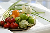 Tomatillos, chillies and spring onions on plate