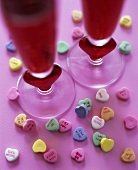 Heart-shaped sweets and two glasses of red cocktail