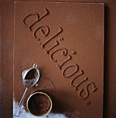 The word 'delicious' in chocolate dusted with cocoa powder