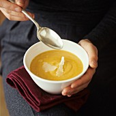 Person holding a bowl of pumpkin soup with Parmesan shavings