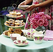 Woman putting cakes and tea things on garden table