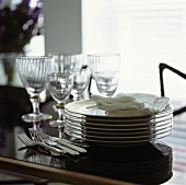 Pile of plates, cutlery and glasses on a dining table