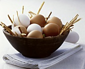 Brown and white eggs in a wooden bowl
