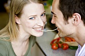 Young couple eating the same strand of spaghetti