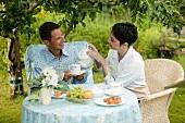 Young couple having breakfast in garden