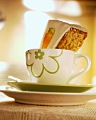 A piece of carrot cake in a coffee cup