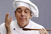 Contented chef with wooden spoon in his hand