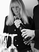 Opening a bottle of sparkling wine, blond woman in background