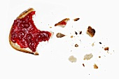 A slice of bread and jam, partly eaten