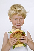 Blond boy holding salami and cheese sandwich in his hands