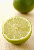 Half a lime with whole lime in background