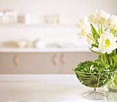 Spinach in wire basket and vase of tulips in a kitchen