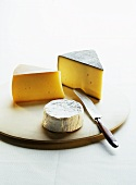 Three kinds of cheese on a wooden board