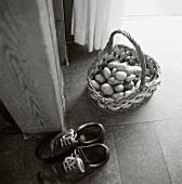A basket of potatoes in hallway, shoes beside it