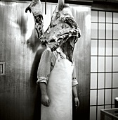 Butcher behind hanging pieces of meat