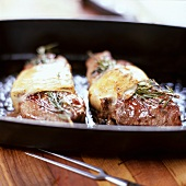 Steaks topped with rosemary and melted cheese