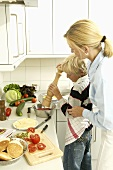 Woman with blond boy seasoning tomatoes
