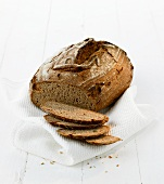 A loaf of rye bread, partly sliced