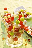 Melon balls and mozzarella on wooden skewers in glass