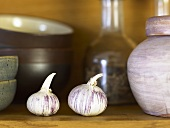 Two garlic bulbs on a kitchen shelf
