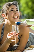 Smiling woman having a glass of rosé wine poured
