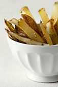 Baked potato wedges in a white bowl