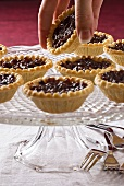 Hand reaching for a mince tart on a cake stand