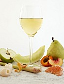 A glass of white wine surrounded by fruit