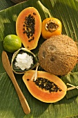 Halved papaya and coconut on a banana leaf