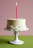 Cake with one candle on a cake stand