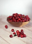 Cranberries in and in front of a small bowl