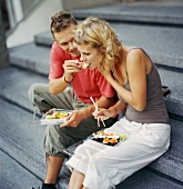 Young couple sitting on steps eating sushi