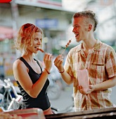 Young couple eating chocolate fruit skewers