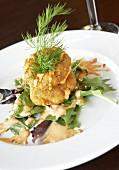 Crab cakes with cocktail sauce on salad leaves
