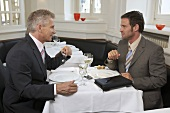 Two businessmen in conversation in a restaurant