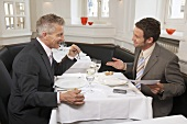 Two men negotiating while eating in a restaurant