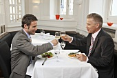 Two men clinking glasses of wine over meal