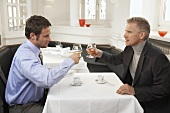 Two men drinking cognac and espresso in a restaurant