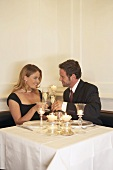 Young couple clinking glasses of champagne in restaurant