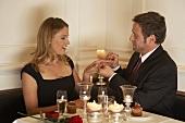Junger Mann steckt Frau einen Ring an