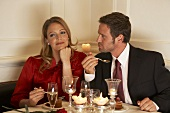 Man and young woman enjoying dessert after evening meal