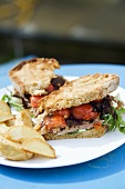 Steak and tomato sandwich with potato wedges